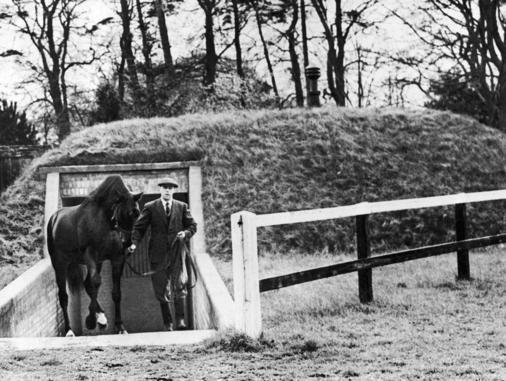 Nearco, the highest priced racehorse ever sold (?65,000), has a bomb-proof shelter at this town near Newmarket, Cheveley, England on April 16, 1944. The shelter has air conditioning, electric lighting, and is roofed with 4 ft. of reinforced concrete surmounted by several feet of earth. Here, Nearco is shown being led out of his shelter. (AP Photo)