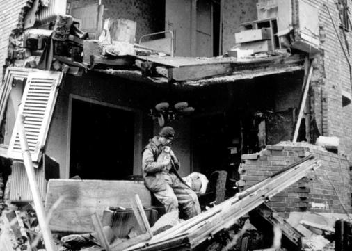 British trooper W. Williamson rescues a puppy from the ruins of a shell-damaged house in Geilenkirchen, Germany, in November 1944. (AP Photo)