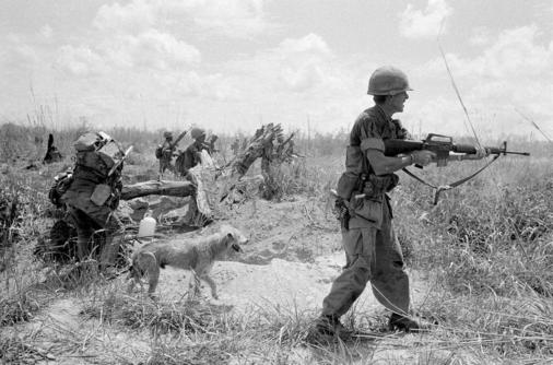 U.S. Adviser Lt. Col. Burr M. Willey of Ayer, Mass., fired his rifle as he moved up Route 13 with a South Vietnamese army unit toward An Loc, besieged provincial capital north of Saigon. In this scene in Vietnam, May 19, 1972, Willey was followed by his faithful dog Moose and South Vietnamese troops. On June 19, the colonel and his dog were killed during a rocket attack in the area along Route 13. (AP Photo/Nick Ut)